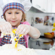 Cute little girl in apron cooking cookies — Stock Photo