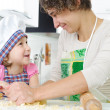 Stock Photo: Young mother with little daughter preparing cookies