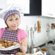 Cute little girl holding plate with cookies - Stock Photo