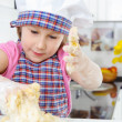Stock Photo: Little girl kneading dough