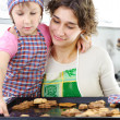 Foto Stock: Little girl and mother with baked cookies