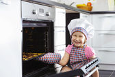 Cute little girl put cookies in stove — Stock Photo