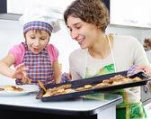 Kleine mädchen und mutter mit gebackene kekse — Stockfoto