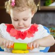 Cute little girl rolling clay dough with — Stock Photo