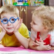 Funny brother in toy glasses with sister on floor — 图库照片