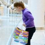 Cute little boy with shopping bags near handrail — Stock Photo