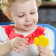 Little girl making a star shape from clay dough — Stock Photo