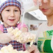 Little baker cooking in kitchen with mother — Stock Photo