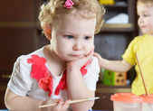 Thoughtful little girl with paintbrush — Stock Photo