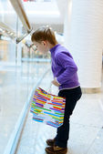Cute little boy with shopping bags near handrail — Stock Photo