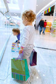 Children with bags in mall — Stock Photo