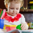 Little girl playing with clay dough — Stock Photo