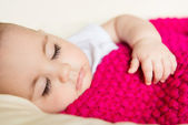 Sleeping baby covered with knitted blanket — Stock Photo