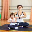 Young mother and little daughter exercising in gym — Stock Photo