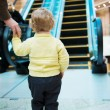 Little girl standing in front of escalator - Stock Photo