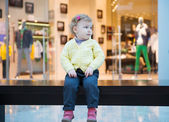 Lost girl sitting on bench in mall — Stock Photo