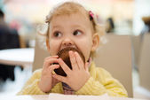 Cute girl eating muffins in cafe — Stock Photo