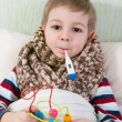 Sick little boy lying in bed with thermometer — Stock Photo #22376117