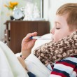 Sick little boy lying in bed with thermometer — Stock Photo #22376399