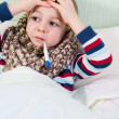 Sick little boy lying in bed with thermometer — Stock Photo #22376409