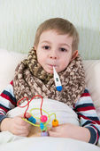 Sick little boy lying in bed with thermometer — Stock Photo