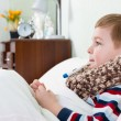Sick little boy lying in bed with thermometer - Stock Photo
