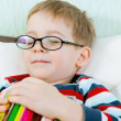 Little tired boy sleeping with book in bed - Stock Photo