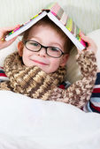 Cute boy with book above his head — Stock Photo