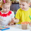 Llittle brother and sister painting at home — Stock Photo #23562795