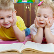Royalty-Free Stock Photo: Cute little brother and sister reading book on floor