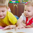 Cute little brother and sister reading book on floor — Stock Photo