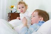 Little girl and her sick brother lying in bed — Stock Photo