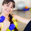 Young smiling woman exercising with dumbbells — Stock Photo #23753137