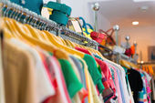 Variety of clothes hanging on rack — Stok fotoğraf