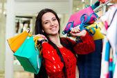 красивая улыбаясь молодая девушка, холдинг сумки для покупок — Стоковое фото