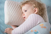 Sick and tired girl liying in bed on pillow — Stock Photo