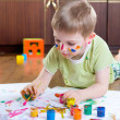 Little boy painting with colorful paints — Stock Photo
