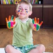 Cute little boy showing his colorful palms — Stock Photo