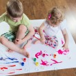Little brother and sister painting on floor — Stock fotografie