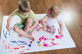 Little brother and sister painting on floor — Stock Photo