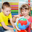 Little children study globe - Stock Photo