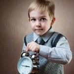 Cute little boy holding alarm clock — Stock Photo #25369379