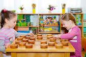 Dvě malé holčičky hrají v dáma — Stock fotografie