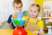 Little children study globe — Stock Photo