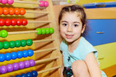 Cute little girl playing with abacus — Stock Photo