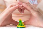 Condom in heart doing by womans hand — Stock Photo