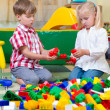 Two children playing with blocks on the floor — Stock Photo