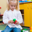 Little blonde girl playing with building bricks in preschool — Stock Photo