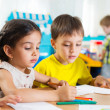 Stock Photo: Cute preschoolers drawing with colorful pencils