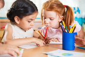 Cute preschoolers drawing with colorful pencils — Stock Photo
